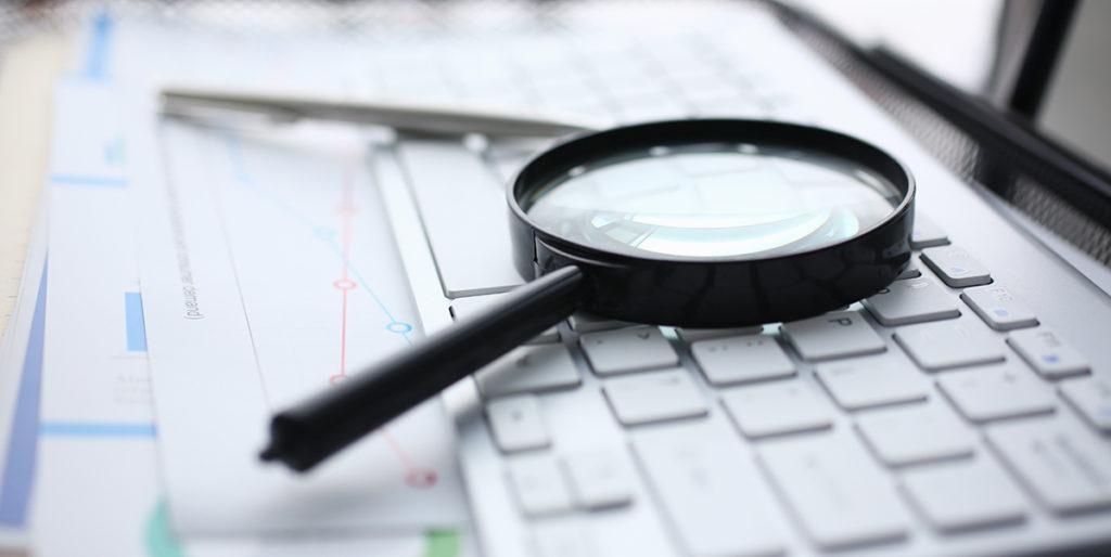 magnifying glass lies white keyboard